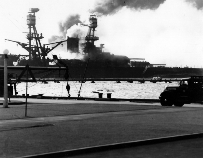 Nevada heading down the channel, afire from several Japanese bomb hits, as seen from Ford Island during the latter part of the attack. Ship whose boom and flagstaff are visible at left is Avocet (AVP-4). Note camouflage Measure 5 false bow wave painted on Nevada. (U.S. Navy Photograph 80-G-32443 National Archives and Records Administration, Still Pictures Division, College Park, Md.)