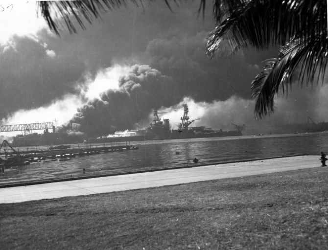 Nevada afire off the Ford Island seaplane base, with her bow pointed up-channel. Shaw (DD-373) burning in the floating dry dock YFD-2 is in the left background. Photographed from Ford Island, with a dredging line at left. (U.S. Navy Photograph 80-G-32457 National Archives and Records Administration, Still Pictures Division, College Park, Md.)