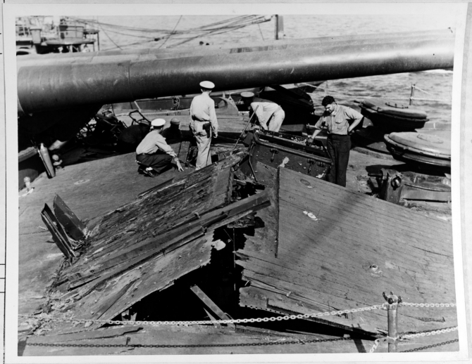 Damage to the forecastle deck of Nevada, caused by the explosion of a Japanese bomb below decks. Gun barrels of the battleship's forward 14/45 triple turret are in the background. Photographed on 12 December 1941 from on board Rail (AM-26), which was tied up alongside Nevada's starboard bow, assisting with salvage efforts. Note officer in center, wearing a .45 caliber pistol. (Naval History and Heritage Command Photograph NH 64484)