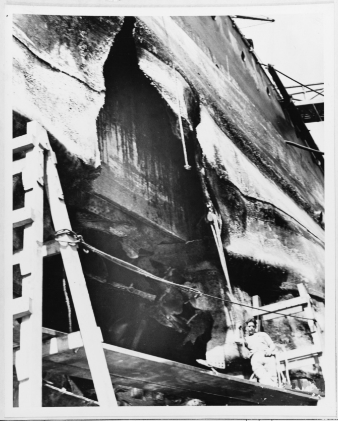 Hole in the ship's port side, between about Frame 38 and Frame 46, caused by a Japanese Type 91 aerial torpedo that hit her during the 7 December 1941 air raid. Photographed about 19 February 1942. The battleship's side armor is visible inside the hole's upper section. (Naval History and Heritage Command Photograph NH 64306)