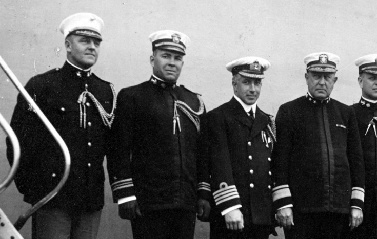 Commander, Sixth Battle Squadron and his staff. The following staff members are pictured on board New York on 1 May 1918. From left to right, Maj. Nelson P. Vulte, USMC; Lt. Cmdr. Jonas H. Ingram; Capt. N.E.F. Aylmer, RN; Rear Adm. Rodman; Cmdr. Husband E. Kimmel; Cmdr. E. W. Money, RN; Lt. Chauncey A. Lucas; and Lt. Harold Dodd. (Naval History and Heritage Command Photograph NH 52739)