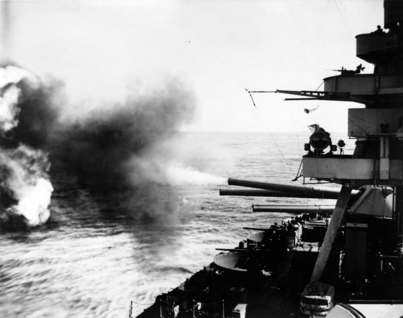 New York bombarding Japanese defenses on Iwo Jima, 16 February 1945. She has just fired the left-hand 14/45 gun of Turret IV. View looks aft, on the starboard side. (U.S. Navy Photograph 80-G-308952, National Archives and Records Administration, Still Pictures Division, College Park, Md.)
