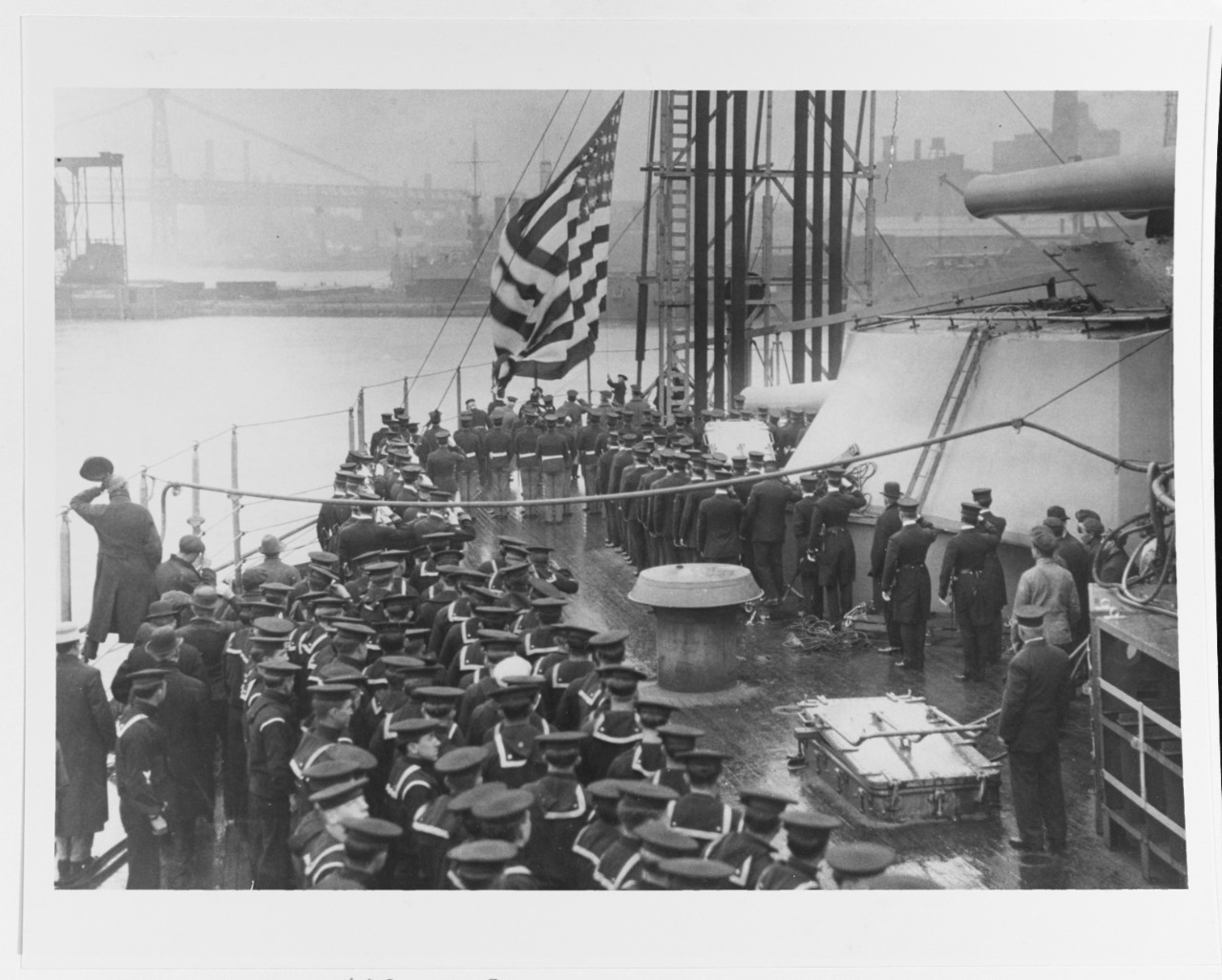 The National Ensign is raised at New York's stern during her commissioning ceremonies, 15 April 1914, at the New York Navy Yard, Brooklyn, N.Y. Courtesy of the Naval Historical Foundation, 1975. (Naval History and Heritage Command Photograph NH 83711)