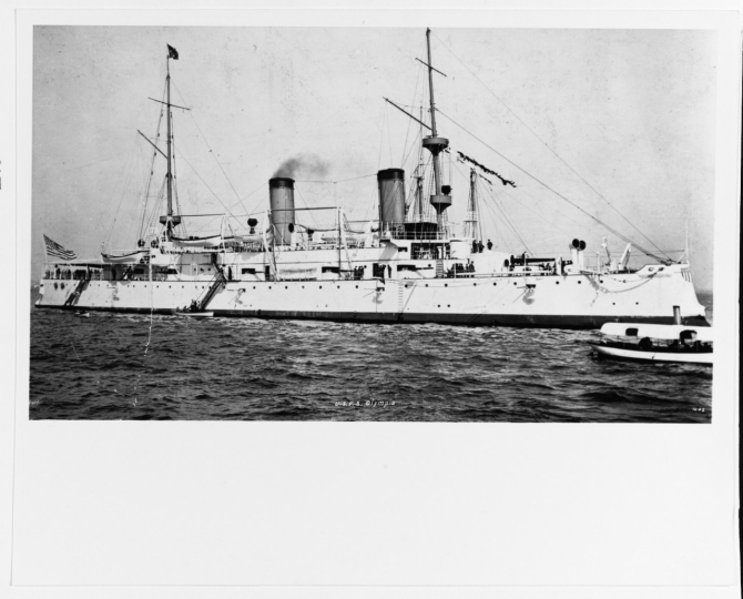 The ship, repainted in her white and spar color scheme, flies Dewey's flag as she participates in the Dewey Day Naval Parade in New York harbor, 29 September 1899. (Photographed by Hart, U.S. Navy Photograph NH 2894, Photographic Section, Naval History and Heritage Command)
