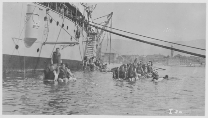 Men of the ships company swim alongside their cruiser in the Adriatic at Spalato. (R.E. Wayne I-20, undated U.S. Navy Photograph NH 122997, Photographic Section, Naval History and Heritage Command)