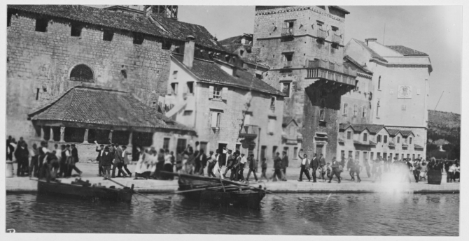 People greet the bluejackets and marines from Olympia as they land at Trogir (Traù), Dalmatia, 23 September 1919. Some of the people welcome the Americans joyfully, while others look on with apprehension. Note the traditional buildings and their narrow streets, that hinder the landing. (Wayne L-85, U.S. Navy Photograph NH 121370, Photographic Section, Naval History and Heritage Command)