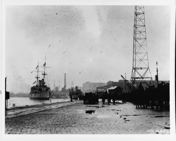 Olympia arrives at the Washington Navy Yard carrying her sacred charge on the otherwise dreary day, 9 November 1921. Destroyers Barney (DD-149) and Blakeley (DD-150) are just visible immediately beyond Olympia's bow. (Courtesy of Edward Page, 1979, U.S. Navy Photograph NH 89731, Photographic Section, Naval History and Heritage Command)
