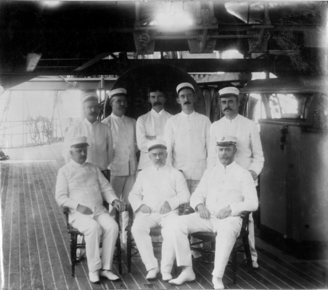 Staff and junior officers on board Olympia in Manila Bay, c. 1898. Those present include (seated left to right): Medical Inspector Abel F. Price; Pay Inspector Daniel A. Smith; and Capt. William P. Biddle, USMC; (standing left to right): Passed Assistant Surgeon John E. Page; unidentified; Assistant Engineer Edward H. De Lany (or Naval Constructor Washington L. Capps); Lt. Stokely Morgan; and Lt. (j.g.) Samuel M. Strite. (Unattributed or dated U.S. Navy Photograph NH 43348, Photographic Section, Naval History and Heritage Command)