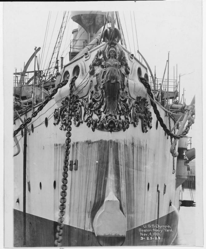 A bow shot of the ship while at Boston Navy Yard shows her gilded bronze figurehead, sculpted by Augustus Saint-Gaudens and commemorating her victory at Manila Bay, 4 November 1901. (Courtesy of Bureau of Construction and Repair, 1925, U.S. Navy Photograph NH 43048, Photographic Section, Naval History and Heritage Command)