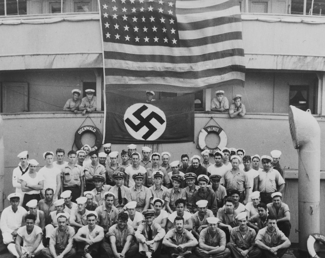 Omaha's boarding party, Lt. George K. Carmichael (in the center with white cap cover), poses beneath the Stars and Stripes displayed over the German flag on board the captured blockade runner Odenwald, 18 November 1941. Note life rings ODENWALD HAMBURG and WILLMOTO PHILADELPHIA (U.S. Navy Photograph 80-G-464023, National Archives and Records Administration, Still Pictures Branch, College Park, Md.)