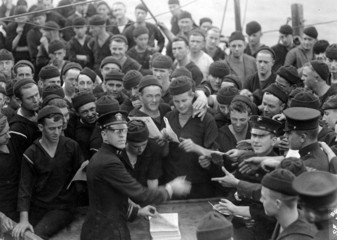 Chaplain distributing the Pennsylvania ship's newspaper to sailors and marines of her crew, circa 1918. Almost all the sailors present are wearing knitted watch caps. (Naval History and Heritage Command Photograph NH 3027)