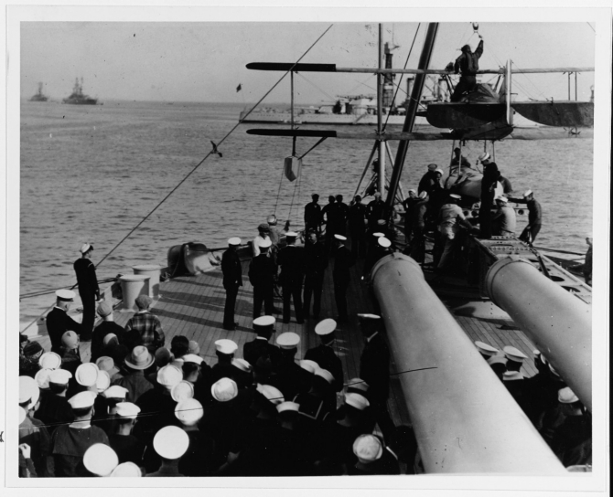 American humorist Will Rogers (hatless, in center) talks with some of the ship's officers on the quarterdeck, on board Pennsylvania, March 1928. Note men at right placing a Vought UO-1 aircraft on the catapult. Courtesy of the Naval Historical Foundation, Collection of Adm. Montgomery M. Taylor. (Naval History and Heritage Command Photograph NH 42749)