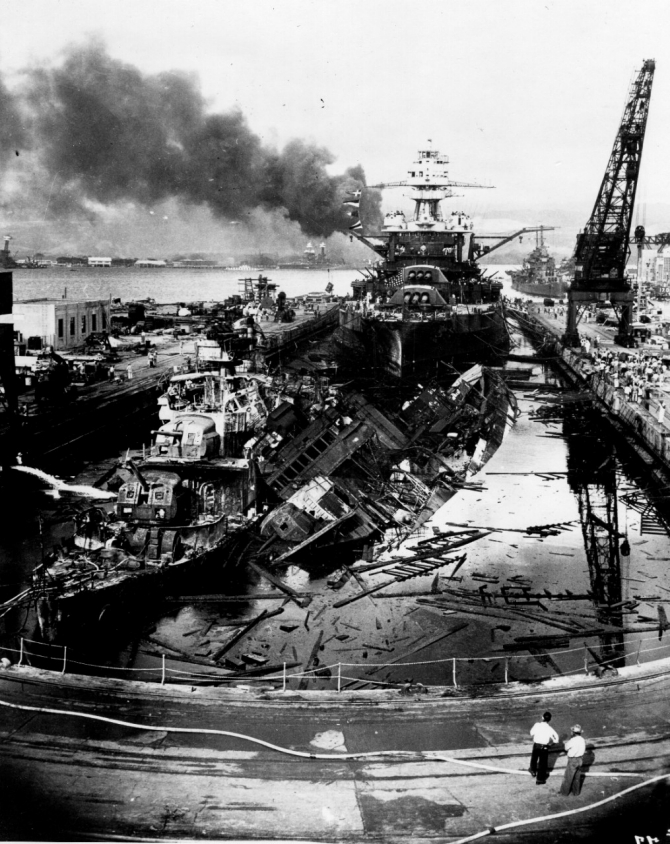 The wrecked destroyers Downes (DD-375) and Cassin (DD-372) in Dry Dock No. 1 at the Pearl Harbor Navy Yard, soon after the end of the Japanese air attack. Cassin has rolled off her blocks onto her sistership Downes. Pennsylvania lies astern, occupying the rest of the dry dock. The torpedo-damaged cruiser Helena (CL-50) is in the right distance, beyond the crane. Visible in the center distance lies the capsized Oklahoma (BB-37), with Maryland (BB-46) alongside. Smoke is from the sunken and burning Arizona (BB-39), out of view behind Pennsylvania. California (BB-44) is partially visible at the extreme left. This image has been attributed to Photographer's Mate Harold Fawcett. (U.S. Navy Photograph 80-G-19943, National Archives and Records Administration, Still Pictures Division, College Park, Md.)