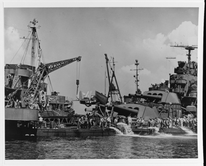 Pennsylvania low in the water and under salvage, after being torpedoed in Buckner Bay, Okinawa, 12 August 1945. A salvage tug is alongside, assisting. Note hoses run through her 14-inch/45 guns to help bring water from below decks. Note Curtiss SC-1 floatplane on her deck. The censors obliterated the ship's radar antennas in this photo. (U.S. Navy Photograph 80-G-490327, National Archives and Records Administration, Still Pictures Division, College Park, Md.)