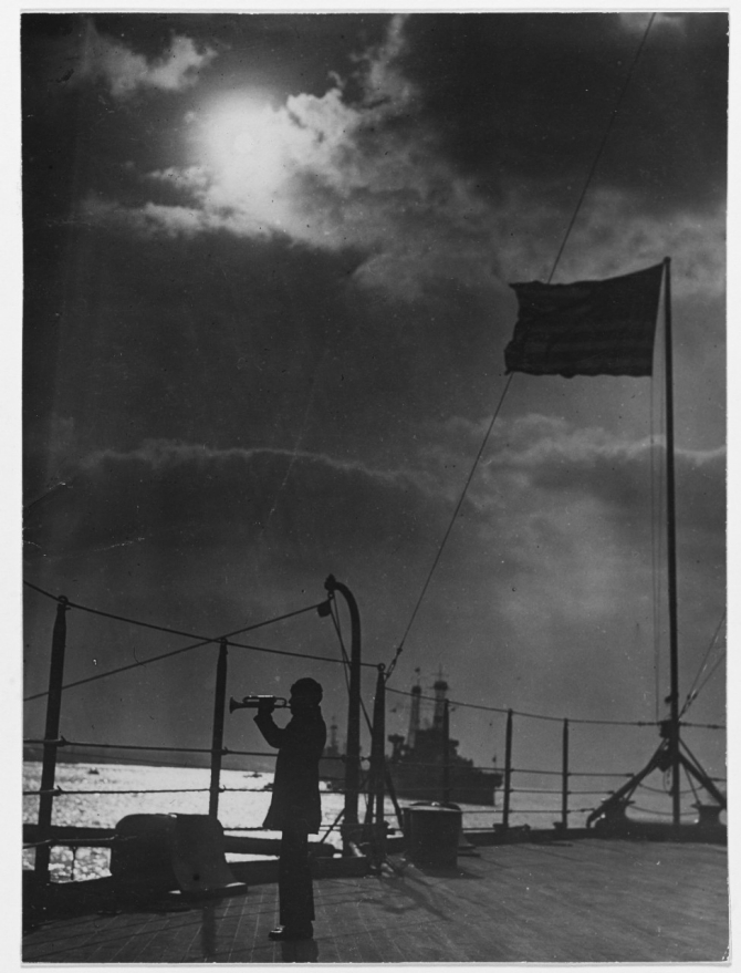 A bugler sounds a call on Pennsylvania's fantail, circa 1918.  Other units of the Battle Fleet are in the background. (Naval History and Heritage Command Photograph NH 42746)