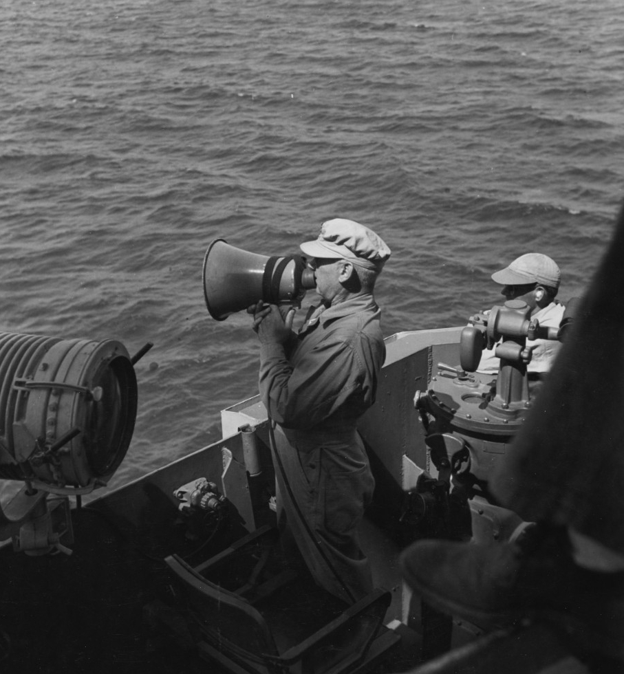Rear Adm. Berkey speaks to another ship via electric megaphone (or loud hailer) from the bridge of his flagship, Phoenix, as the Allied vessels shell Corregidor, 15 February 1945. The original caption identifies the ship as Australia, but she does not fight in the battle and Berkey most likely is hailing Shropshire, which displays a somewhat similar silhouette. (U.S. Navy Photograph 80-G-273279, National Archives and Records Administration, Still Pictures Division, College Park, Md.)