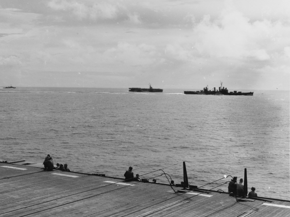 A carrier crewman snaps this shot of a starboard beam view of Phoenix (right) as she screens escort carriers off Leyte, 30 October 1944. Note the flight deck sailors gazing at the ships arrayed, and the barriers rigged in the foreground. (U.S. Navy Photograph 80-G-309448, National Archives and Records Administration, Still Pictures Division, College Park, Md.)