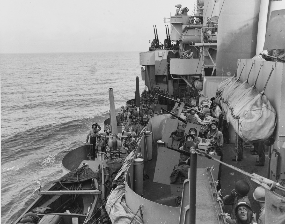 Men manning Phoenix's port side 20 and 40-millimeter guns display the strain of the kamikaze attacks as they look skyward to identify a plane flying overhead while the ship steams to Mindor, 18 December 1944. Note the whaleboat in the lower left, antiflash clothing, and the floater net enclosed in a bag at right. (U.S. Navy Photograph 80-G-47471, National Archives and Records Administration, Still Pictures Division, College Park, Md.)