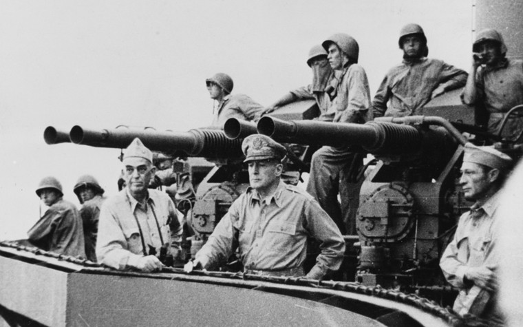 Vice Adm. Kinkaid (left center) and Gen. MacArthur (center) watch the ship bombard the Japanese on Los Negros, 28 February 1944. Col. Lloyd Lehrbas, USA, MacArthur's acting aide, is on the right. Note the quad 40-millimeter gun mount in the background. (U.S. Army Signal Corps SC-188839, National Archives and Records Administration, Still Pictures Division, College Park, Md.)