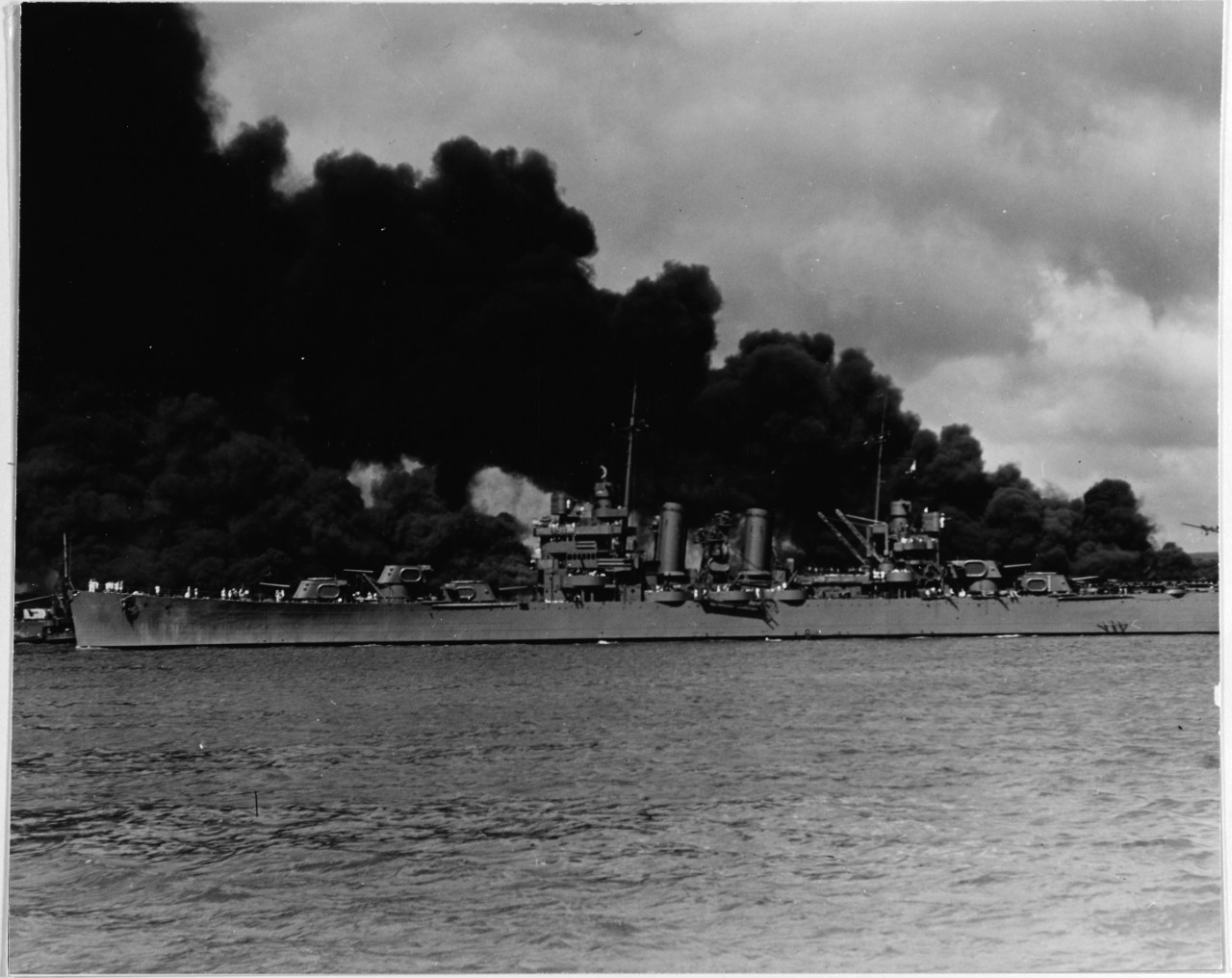Phoenix steams past burning West Virginia (BB-48) (left) and Arizona (BB-39) (right) along the south side of Ford Island as she sorties during the Japanese attack on Pearl Harbor, T.H., 7 December 1941. (Naval History and Heritage Command Photograph NH 50766)