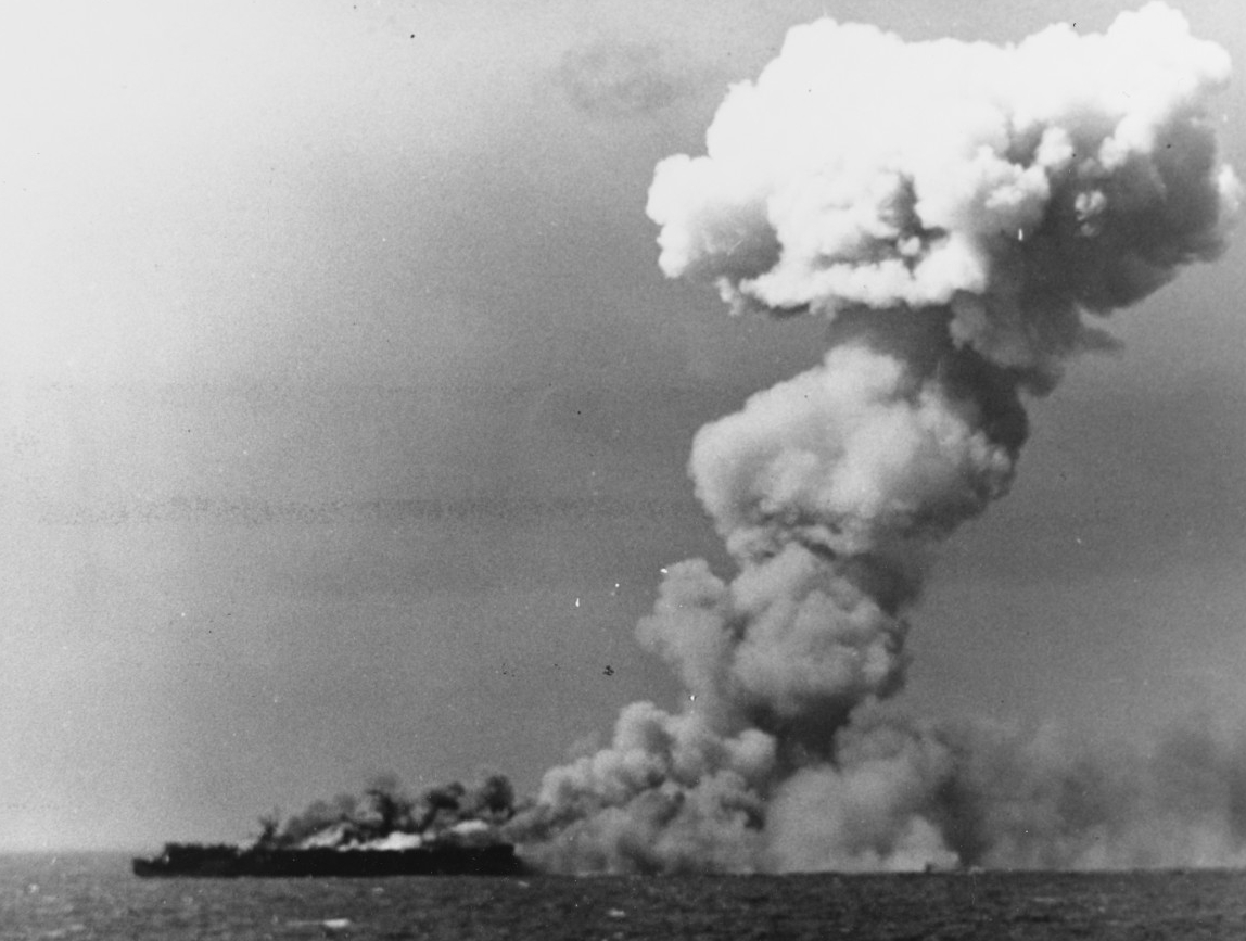 Princeton burns as some of the torpedo warheads in her hangar cook off in a horrific explosion, a huge column of smoke rising from the ship, 24 October 1944. A photographer on board South Dakota snaps this picture, most likely just after the first deadly blast. (U.S. Navy Photograph 80-G-287970, National Archives and Records Administration, Still Pictures Division, College Park, Md.)