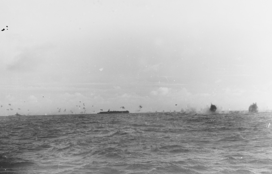 Ships' antiaircraft guns fill the sky with flak bursts as a Japanese plane crashes not far from Princeton off Formosa, 14 October 1944. The battleship in the distance is most likely Alabama (BB-60) or South Dakota (BB-57). (U.S. Navy Photograph 80-G-285050, National Archives and Records Administration, Still Pictures Division, College Park, Md.)