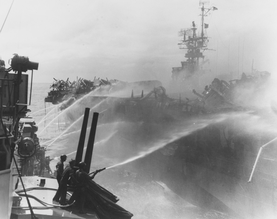 Crewmen on board Birmingham play fire hoses onto the burning carrier as the cruiser closes to render assistance, 24 October 1944. (U.S. Navy Photograph 80-G-270357, National Archives and Records Administration, Still Pictures Division, College Park, Md.)
