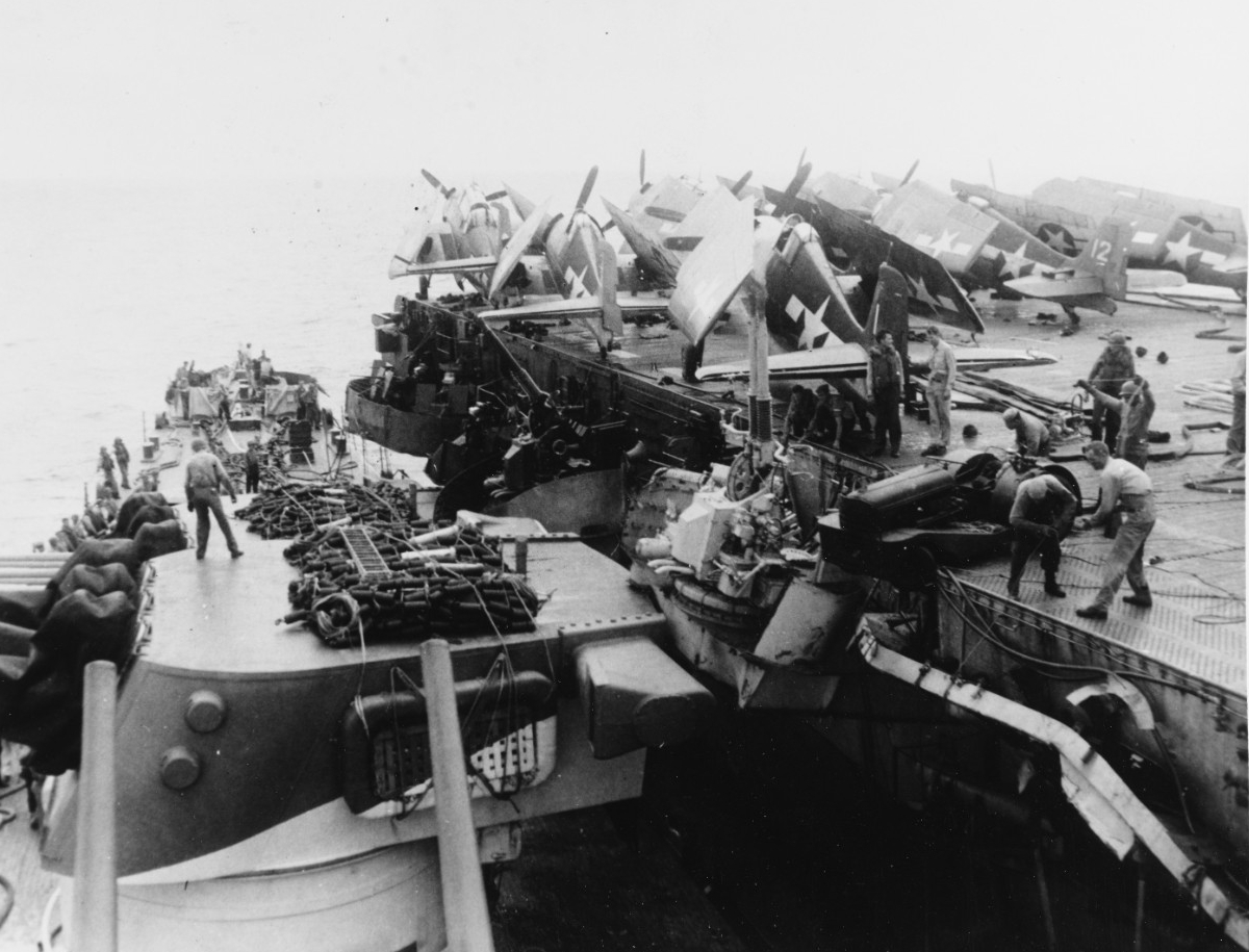 Birmingham (left) helps Princeton (right) during her ordeal, 24 October 1944. The two ships grind together in the swells, and the cruiser's starboard side crushes part of the carrier's portside catwalk and a 40-millimeter gun mount. A flight deck tractor hangs precariously over Princeton's deck edge, and crewmen position Hellcats and Avengers forward. Birmingham trains her forward triple 6-inch gun turret, surmounted by floater nets and life rafts, to port in order to lay alongside the carrier. (U.S. Navy Photograph 80-G-270437, National Archives and Records Administration, Still Pictures Division, College Park, Md.)