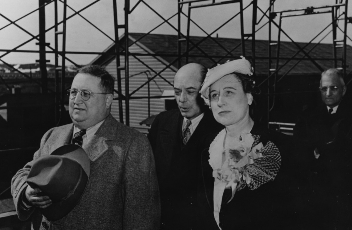 The ship's sponsor party stands at attention as FP-344 slides down the ways at Kewaunee, Wisc., 16 April 1944. Dorothy K. Duvall, the sponsor, is in the right foreground, and also present are Hugh C. Brogan, Vice President and General Manager of Kewaunee Shipbuilding & Engineering Corp., and the Rev. Leonard A Spooner of Kewaunee's Community Congregational Church, who delivers the invocation. (Naval History and Heritage Command Photograph NH 74688)