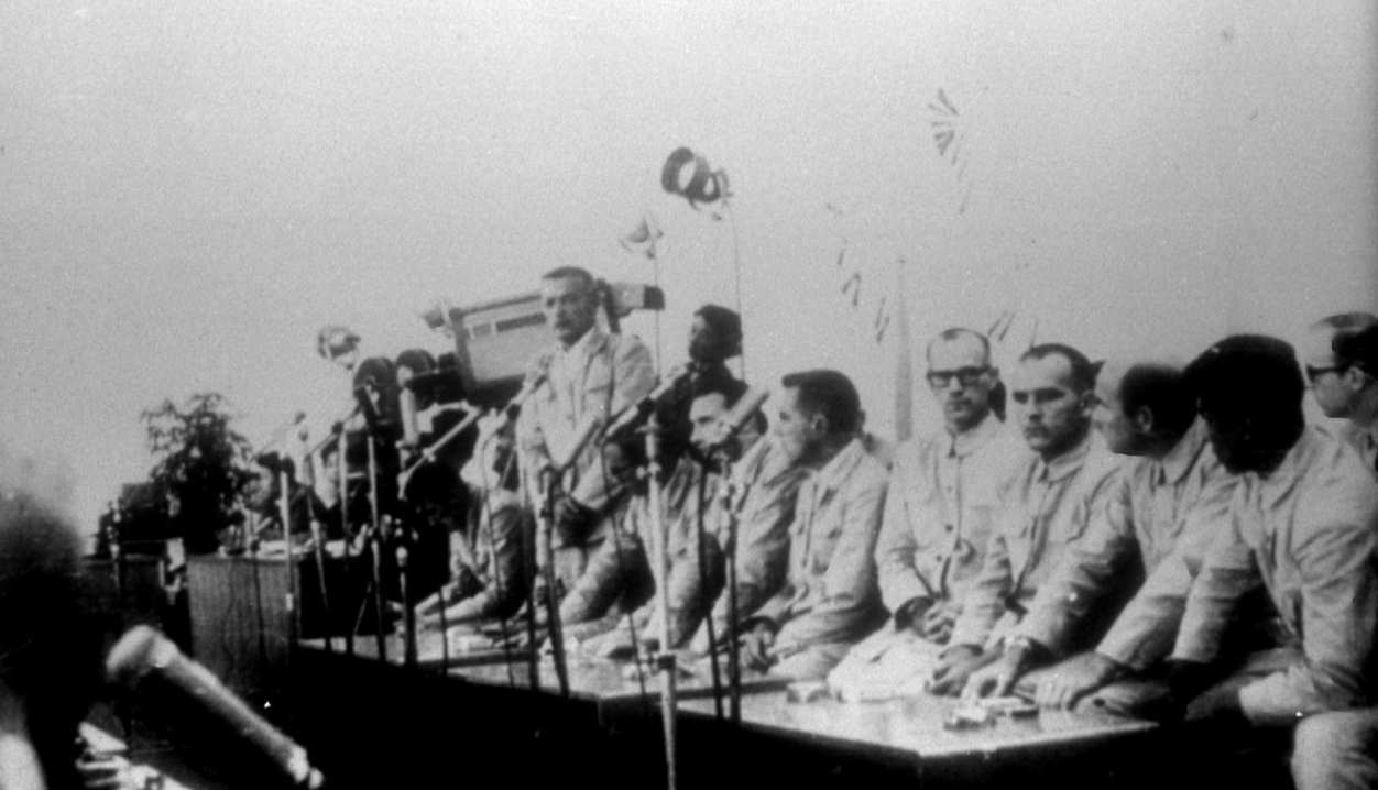 The North Koreans take this propaganda photograph of some of the Pueblo crewmen at a press conference in North Korea, sometime after they capture them. Cmdr. Bucher stands in the center. (Naval History and Heritage Command Photograph NH 75557)