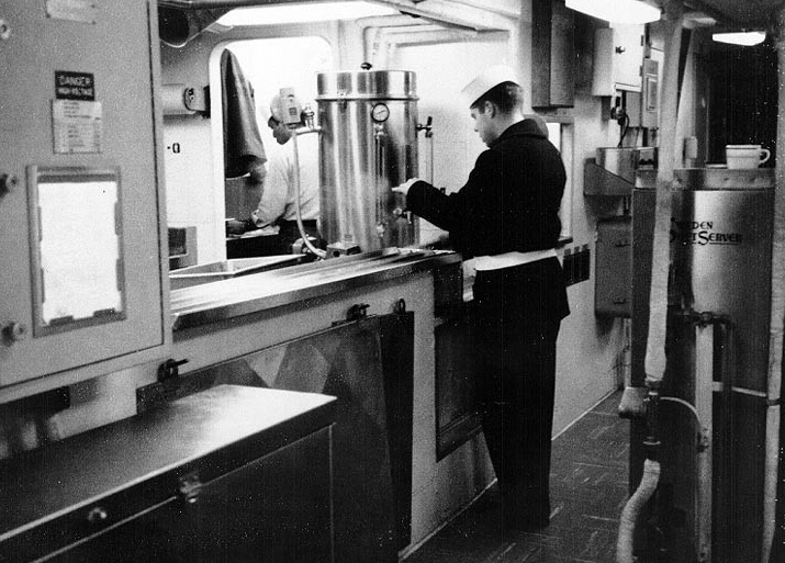A crewman draws a cup of coffee in the ship's mess decks, circa 1967. The sailor wears his coat and belt and is most likely standing a quarterdeck watch, which means that the ship lies moored. (Naval History and Heritage Command Photograph NH 75559)