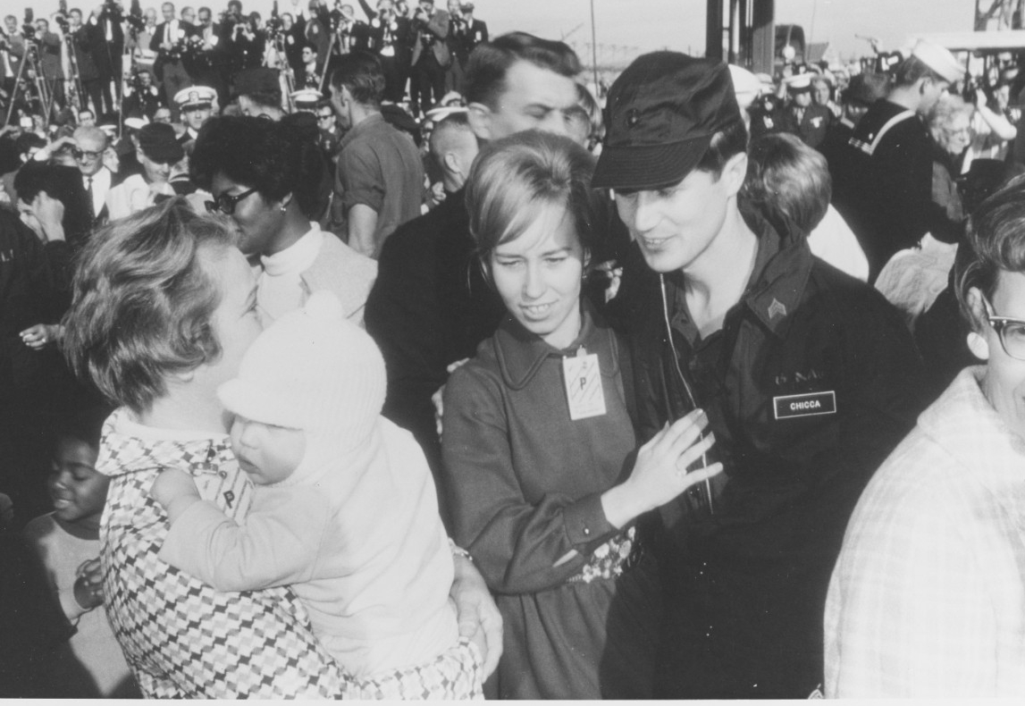 Sgt. Chicca greets his wife, Ann Marie, when the men return home to NAS Miramar on Christmas Eve 1968. Loved ones joyfully and tearfully reunite with the men following their ordeal, and an entourage of journalists film and photograph their homecoming from a stand in the background. (PHC V. O. McColley, Naval History and Heritage Command Photograph K-67346)