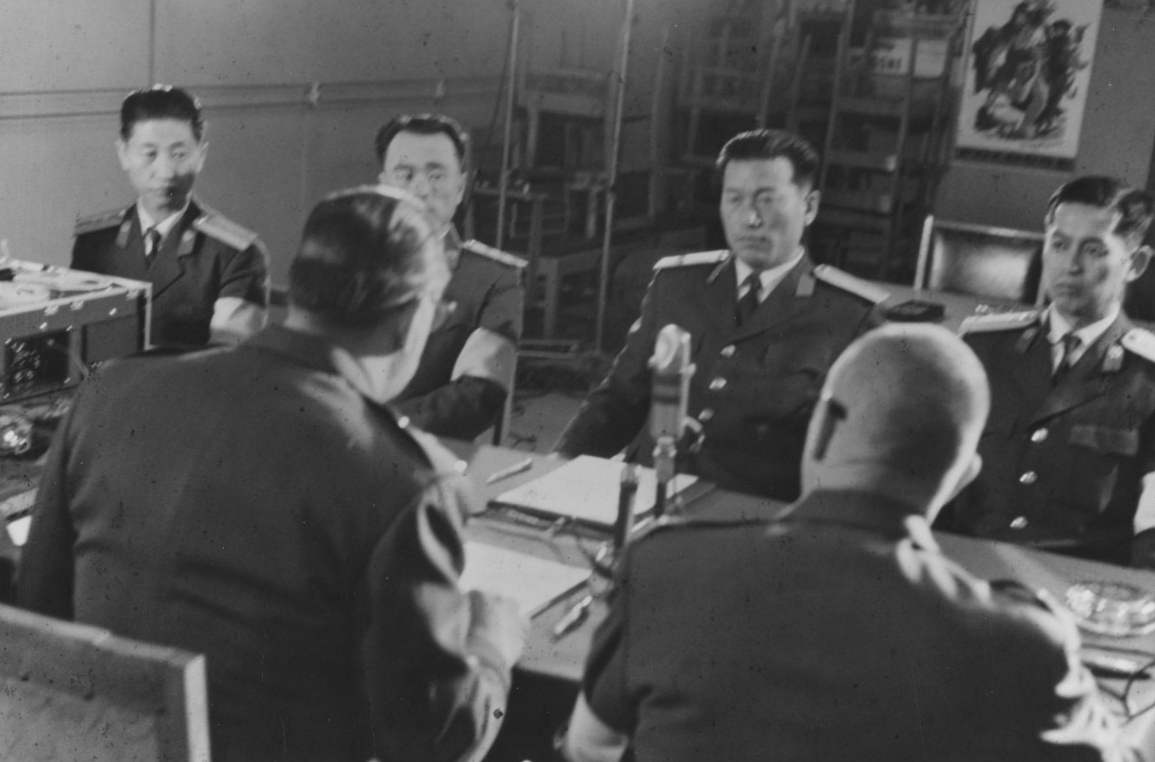 American and North Korean representatives meet at Panmunjom to sign the agreement releasing the men, 22 December 1968. Maj. Gen. Woodward is seated in the left foreground, with his back to the camera. (Naval History and Heritage Command Photograph K-64733)