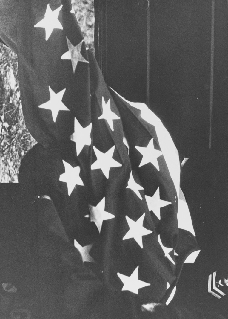 A Navy YN2 holds the U.S. flag that drapes Hodges' coffin when his body returns to the United States, 23 December 1968. (Naval History and Heritage Command Photograph K-64690)