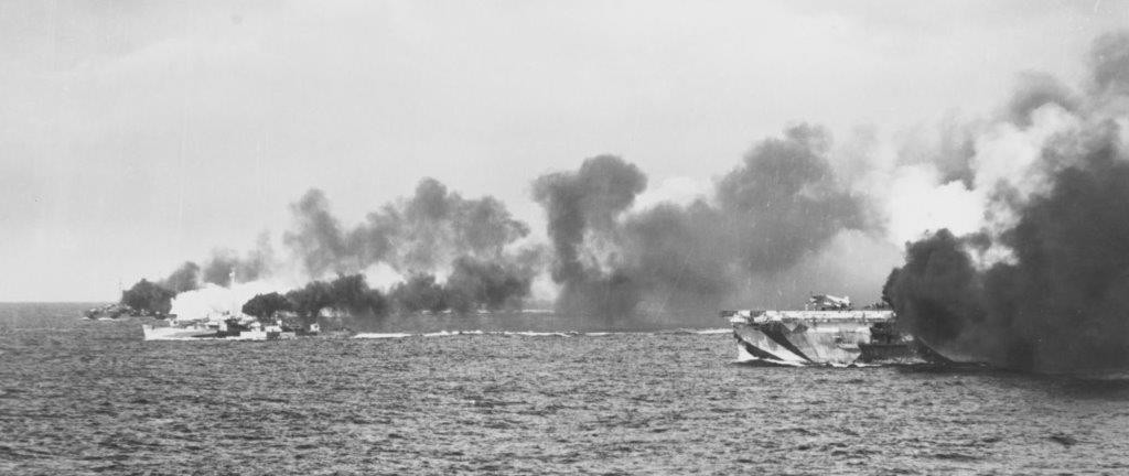 Escort carrier Gambier Bay, Raymond, and another escort vessel of Taffy 3 making smoke at the start of the Battle off Samar, on 25 October 1944. Japanese ships are faintly visible on the horizon. Photographed from escort carrier Kalinin Bay (CVE-68). (U.S. Navy Photograph 80-G-288144, National Archives and Records Administration, Still Pictures Division, College Park, Md.)