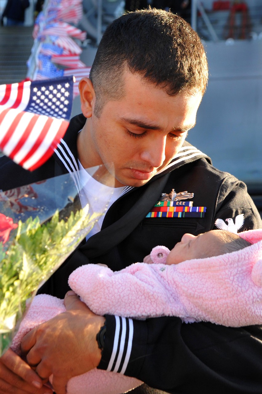 EN2 Stuardo Juarez greets his newborn daughter for the first time when he returns with the ship, 14 December 2011. (MC2 Jacob Sippel, U.S. Navy Photograph 111214-N-AW702-004, Navy NewsStand)