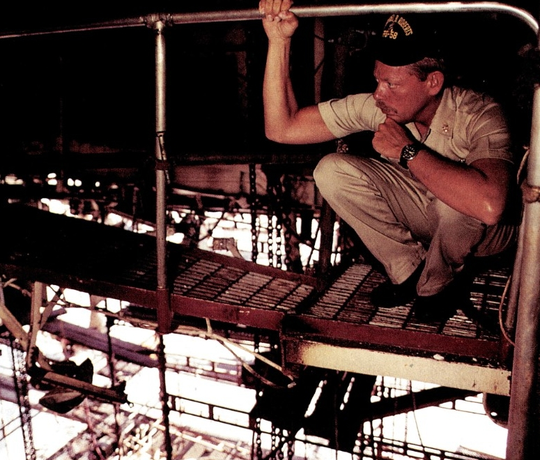 One of the ship's crewmen reflects about the crew's ordeal as he surveys the repair work at Dubai. (PH1 Chuck Mussi, All Hands, August 1988, No. 857, page 15)