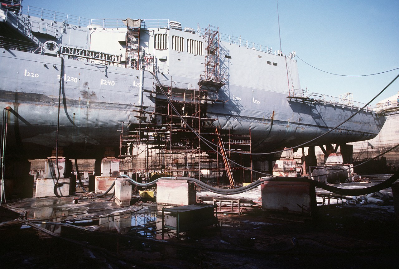 The size of the hole bears mute testimony to the fury of the mine's detonation, while Samuel B. Roberts rests in dry dock at Dubai in the United Arab Emirates. Workers clamber over scaffolding and temporarily make the ship seaworthy for her voyage to the United States. (PH1 Chuck Mussi, All Hands, August 1988, No. 857, page 14)