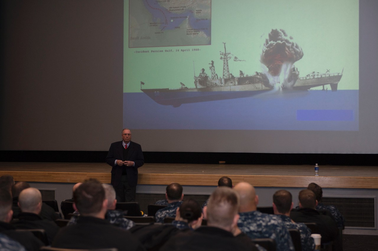 Capt. Rinn (retired) shares his experiences to junior officers during a Surface Warfare Junior Officer Tactical Program summit at Fleet Activities Yokosuka, Japan, 9 February 2015. The image on the screen aptly demonstrates the mine's devastating explosion on that fateful day in 1988. (MC3 Raymond D. Diaz III, U.S. Navy Photograph 150209-N-BB269-036, Navy NewsStand)