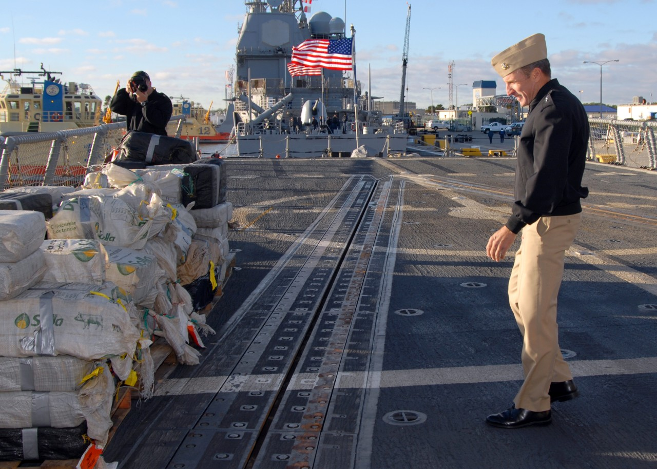 Rear Adm. Joseph D. Kernan, Commander Naval Forces Southern Command and Fourth Fleet, inspects some of the seized cocaine stacked on Samuel B. Roberts' fantail after the ship returns to Mayport, Fla., 12 December 2008. (MC1 Leigh Stilles, U.S. Navy Photograph 081212-N-1522S-005, Navy NewsStand)