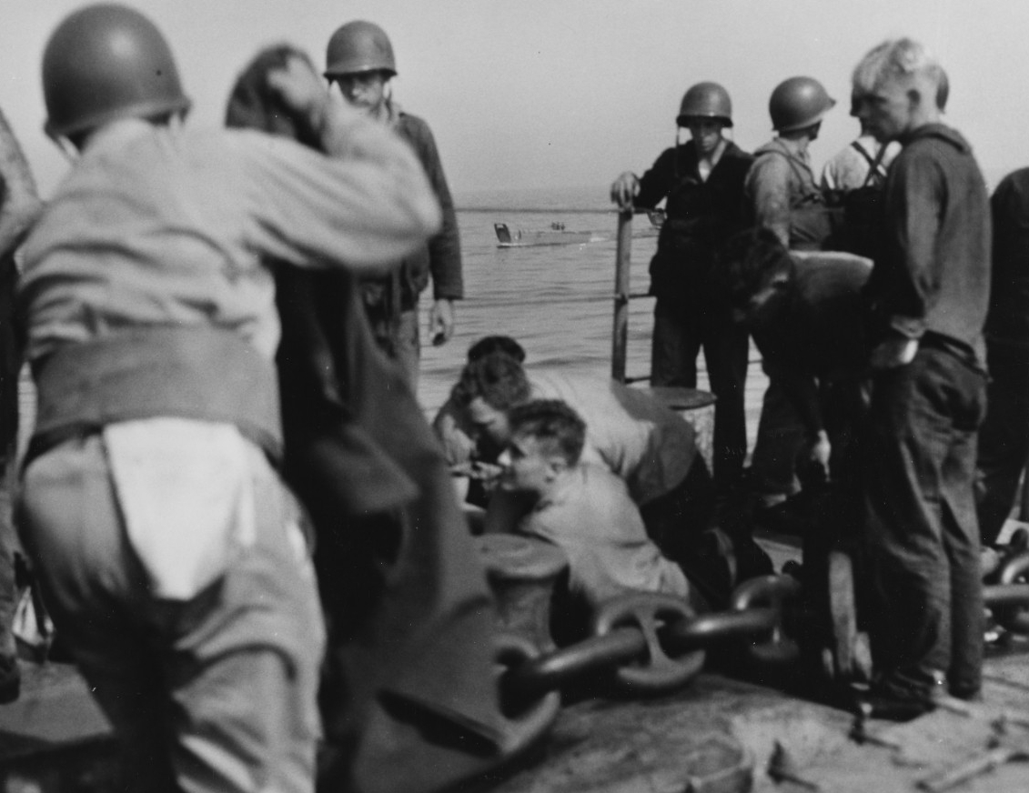 Some of the ship's medical team tend the wounded at an improvised first aid station on the forecastle. (U.S. Navy Photograph 80-G-54355, National Archives and Records Administration, Still Pictures Division, College Park, Md.)