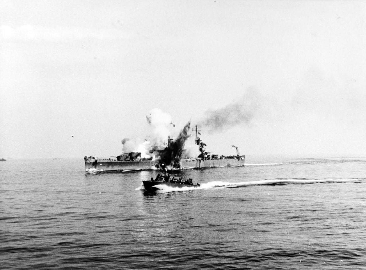 The Fritz-X tears into Savannah's Turret III while she steams off Salerno, at 0944 on 11 September 1943. The bomb penetrates through the turret and deep into her hull and explodes, the blast venting through the top of the turret and also through the ship's hull below the waterline. A motor torpedo boat (PT) passes by in the foreground. (U.S. Navy Photograph NH 95562, Naval History and Heritage Command)
