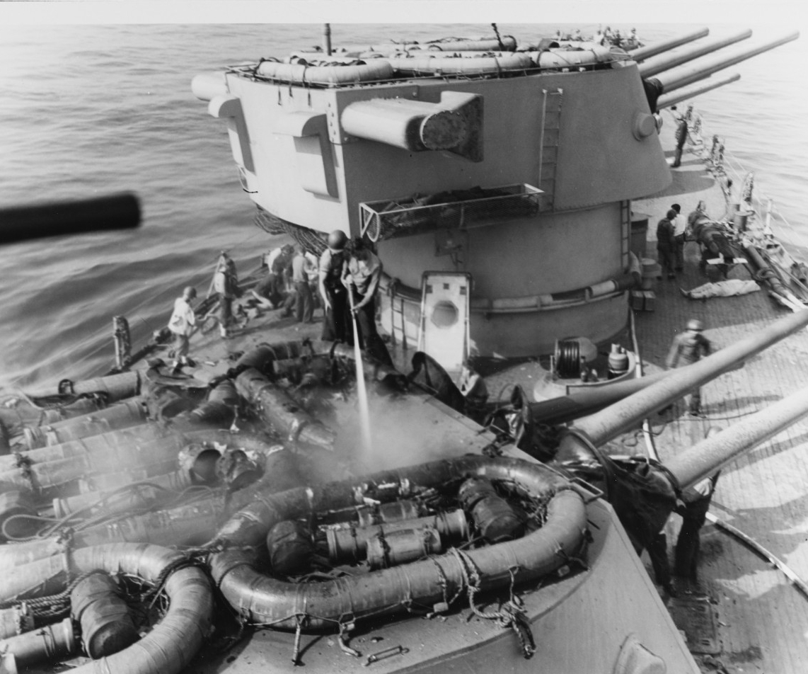 Crewmen spray water into the smoldering turret, and their fellows mournfully lay out casualties (to the right of the picture). (U.S. Navy Photograph 80-G-54357, National Archives and Records Administration, Still Pictures Division, College Park, Md.)