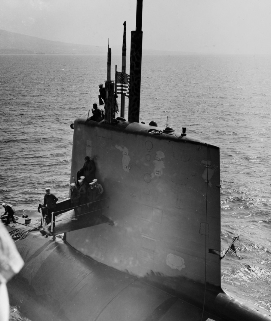 Scorpion pulls alongside advance aviation base ship Tallahatchie County (AVB-2) outside Naples, Italy, 10 April 1968. Cmdr. Francis A. Slattery, the submarine's commanding officer, stands atop her sail, holding a megaphone. (Naval History and Heritage Command Photograph NH 70304)