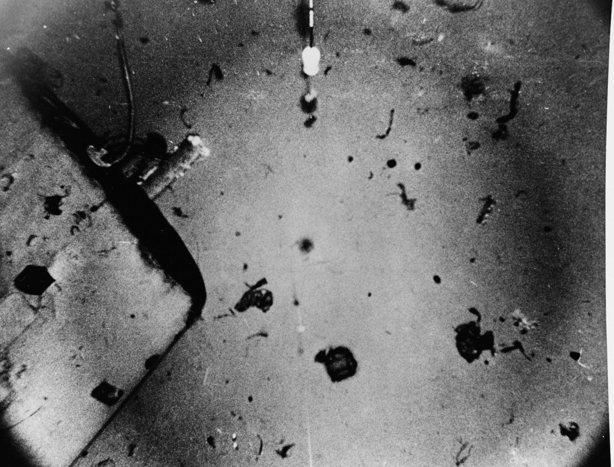 A view of Scorpion's sail, probably taken when Mizar locates the sunken submarine in October 1968, on the Atlantic Ocean floor 10,000 feet deep, some 400 miles southwest of the Azores. This image shows the starboard side of the sail, with its after end at top left, and the starboard access door in lower left. Debris litters the ocean bottom nearby. The device in top center is part of the equipment used in locating and photographing the wreckage. The original photograph bears the date 30 January 1969. (Naval History and Heritage Command Photograph NH 1136656)