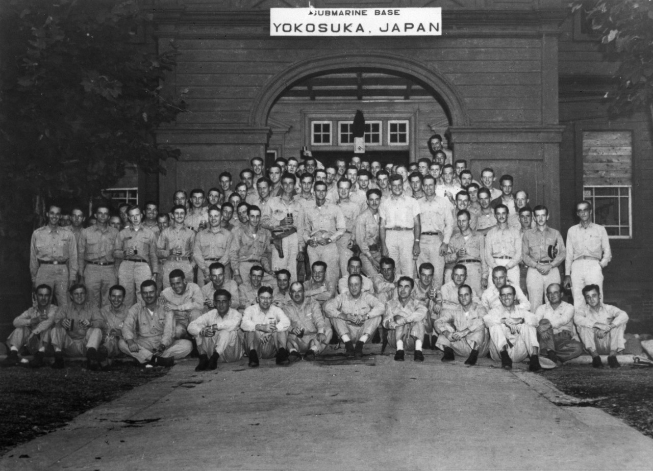 "Vice Adm. Charles A. Lockwood, Commander Submarine Force, Pacific Fleet (seated, center), poses with some of his officers at the newly established Yokosuka Submarine Base, 2 September 1945, while celebrating Japan's formal surrender earlier that day. As identified by Capt. Joseph F. Enright, commanding officer of Dace (SS-247), those seated in the front row include (from left to right): A. C. Smith; Cmdr. Raymond H. Bass, the commanding officer of Runner (SS-275) ; Lt. Cmdr. Stephen L. Johnson, Segundo; Lt. Cmdr. Frank C. Lynch, Jr., Haddo (SS-255); Cmdr. Herman J. Kossler, Cavalla (SS-244); Capt. James A. Jordan, Proteus; H.E. Day; Vice Adm. Lockwood; Capt. Lewis S. Parks, Commander Submarine Squadron 20; Lt. Cmdr. Earle C. Hawk,  Pompon (SS-267); Lt. Cmdr. Rob Roy McGregor, SubRon 6 Staff; Cmdr. Hiram H. Cassedy and Cmdr. William H. Lawrence, Muskallunge (SS-262). Seated immediately behind the front row are (left to right, starting third from left): Cmdr. Alan R. Schnable, Pilotfish (SS-386); Cmdr. John S. McCain, Jr.; Cmdr. Joseph F. Enright, Archer-fish (SS-311); Cmdr. Frank E. Hayler, Hake (SS-256); Cmdr. Richard Holden, Gato (SS-212) ; Lt. Cmdr. Richard H. Bowers, Sea Cat; Cmdr. William B. Sieglaff, Tautog (SS-199) and Cmdr. Bernard F. McMahon, Piper (SS-409). Others present include: Cmdr. Robert K. Kaufman (first standing row, just to left of officer wearing pistol and holding beverage can); Lt. Cmdr. Lloyd R. ""Joe"" Vasey, the executive officer of Angler (SS-240) (first standing row, just to right of officer wearing pistol and holding beverage can); Lt. Cmdr. Paul R. Schratz (first standing row, third to right from Vasey) and Robert D. Quinn (head only is visible, directly behind officer standing, second to right from Schratz). (Naval History and Heritage Command Photograph NH 90518)"