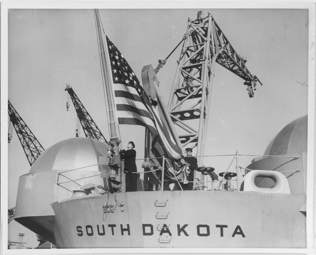 Sailors haul down the colors as South Dakota decommissions at Philadelphia Naval Shipyard, Pa., on 31 January 1947. (U.S. Navy Photograph NH 73929, Naval History and Heritage Command)