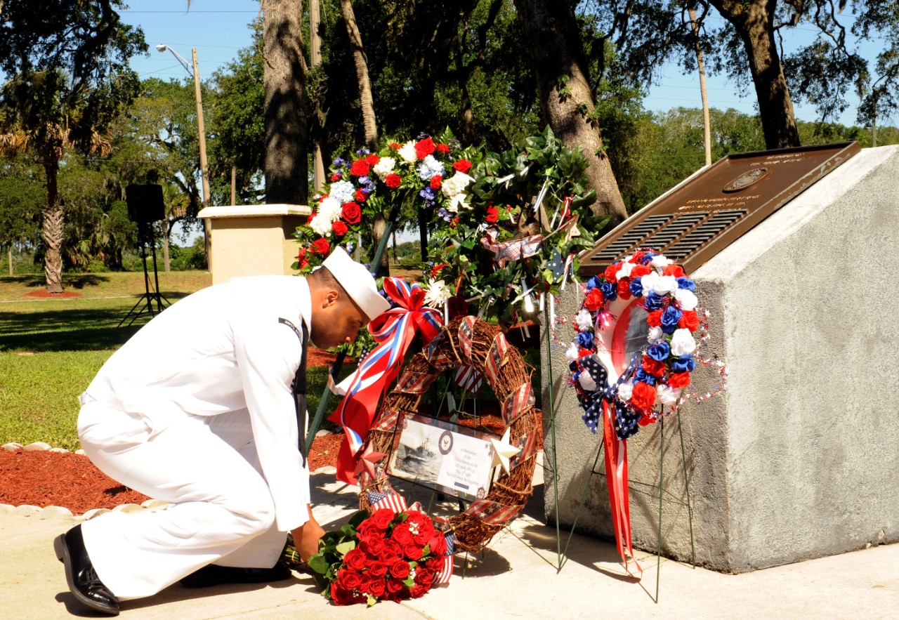 Yeoman 2nd Class DeMario Smith reverently places flowers at the Stark Memorial during the ceremony at Mayport, 16 May 2014. (Mass Communication Specialist 2nd Class Damian Berg, U.S. Navy Photograph 140516-N-TC587-072, Navy NewsStand)