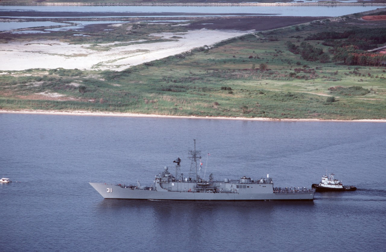 A tug stands by to assist Stark as the frigate resolutely returns to sea for her trials, following the yard work at Pascagoula, Miss, 28 August 1988. The reworked and painted superstructure and hull on the port side indicate the amount of work accomplished to repair the ship from the devastating Iraqi attack. (Lt. Cmdr. Lynn Howell, USNR, Department of Defense Photograph DN-ST-89-01566, Still Pictures Branch, National Archives and Records Administration II, College Park, Md., Photograph 6443021)