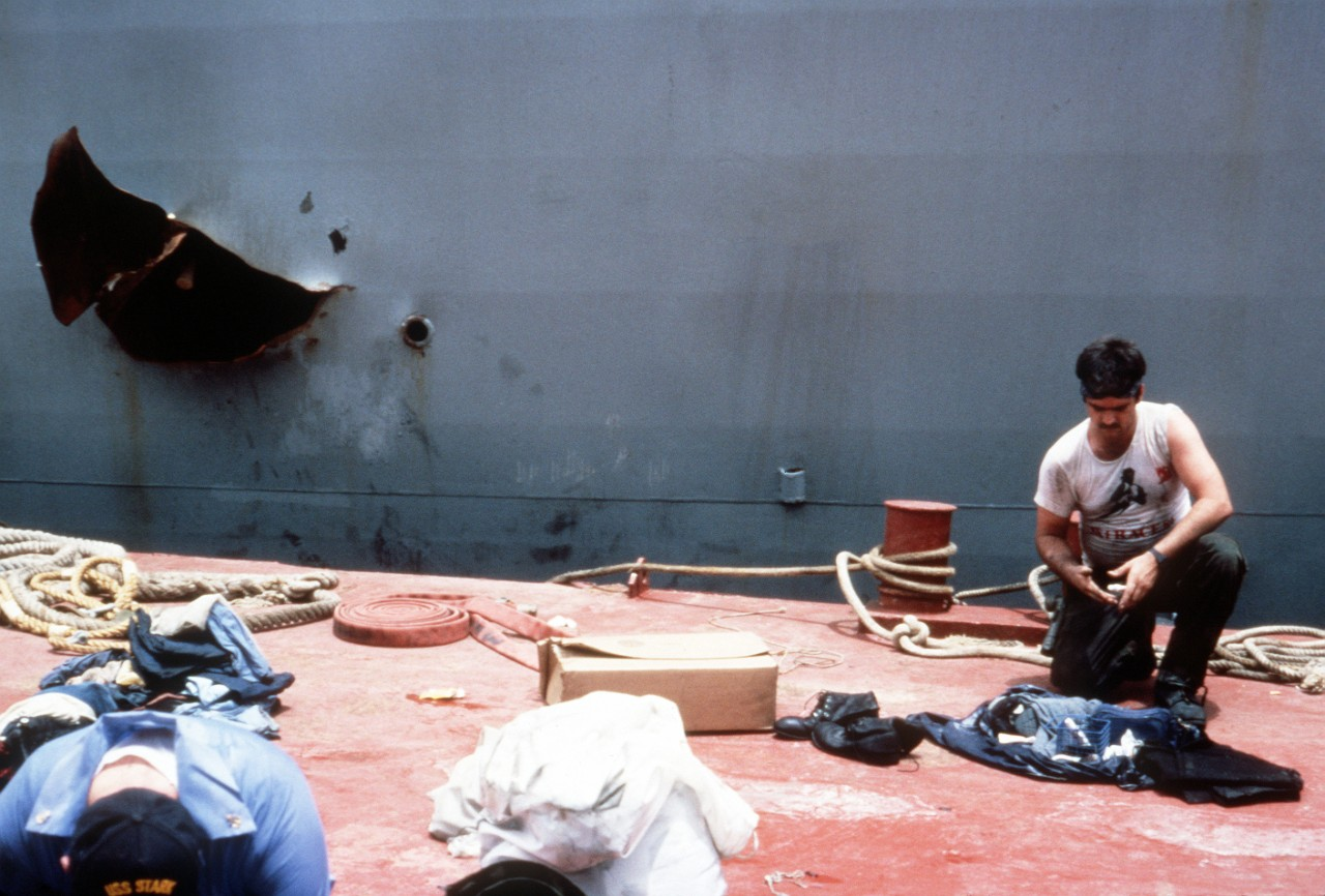 Weary sailors take a break while repairing the ship at Bahrain. The large hole torn into the frigate's port side attests to the devastating impact off the missiles and the resulting fires. (Department of Defense Photograph DN-ST-89-01566, Still Pictures Branch, National Archives and Records Administration II, College Park, Md., Photograph 6443170)